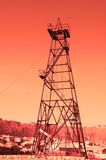Oil derrick. With donkey pump during sunset Stock Image