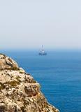 Oil derrick and the cliffs, Malta. Oil derrick and the cliffs and the sea in sunny weather, Malta Stock Images