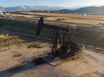 Oil derrick in the desert pumping WTI oil. Royalty Free Stock Photos
