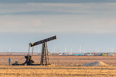 Oil derrick in a golden field with wind turbines in background Stock Photography