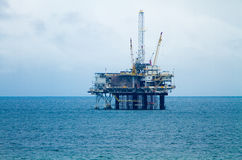 Oil Derrick and Platform On An Overcast Day. Oil rig platform with derrick, cranes, and platform in large expanse of water stock photos