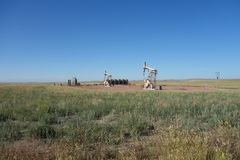 Oil derricks in the prairies. Machines pumping oil from the ground in the flat-lands of wyoming Stock Photography