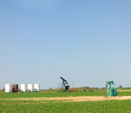 Oil derricks in texas. Oil being pumped and stored on a farm field in america Stock Photography