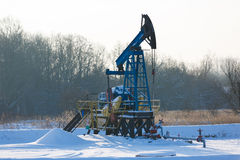 Oil derricks in winter. Oil derricks on snowy field at winter time Stock Image