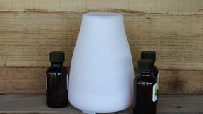 Oil diffuser and essential oil on a wood background stock photography