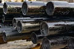 Oil Drill pipe. Rusty drill pipes were drilled in the well section. Downhole drilling rig. Laying the pipe on the deck. View of. The shell of drill pipes laid stock photography