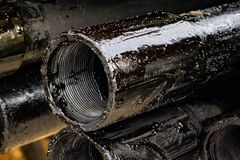 Oil Drill pipe. Rusty drill pipes were drilled in the well section. Downhole drilling rig. Laying the pipe on the deck. View of. The shell of drill pipes laid royalty free stock photo