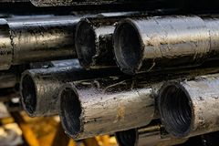 Oil Drill pipe. Rusty drill pipes were drilled in the well section. Downhole drilling rig. Laying the pipe on the deck. View of. The shell of drill pipes laid stock photos