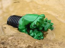 Oil drilling bit in mud. Drill bit used to drill for oil Royalty Free Stock Photos