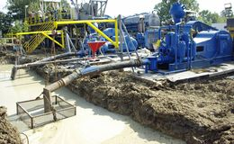 Oil Drilling Mud Pumps. Mud pumps alongside a drilling rig.  Drilling mud is circulated through the hole and is used to remove rock cuttings and other particles Stock Photography