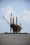 Oil Drilling Platform. In the ocean with two boats underneath Stock Photography