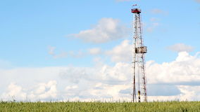 Oil drilling rig and blue sky. Oil drilling rig green wheat and blue sky stock footage