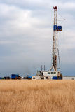 Oil Drilling Rig in a Hay Field. Under a cloudy sky and in a hay field stands an oil drilling rig Stock Images
