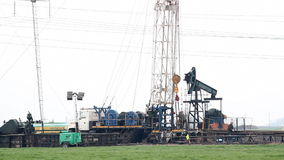 Oil drilling rig on oilfield. Oil drilling rig with workers on oilfield stock footage