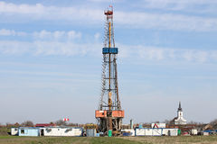 Oil drilling rig with workers near village Stock Images