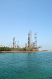 Oil drilling site at the shore Stock Photos