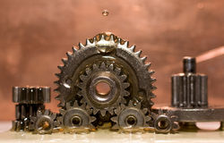 Oil dripping on gear. Lots of small gears with oil dripping on them Royalty Free Stock Photo