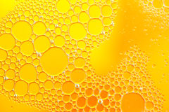 Oil drops floating in water abstract orange color background. Royalty Free Stock Photos