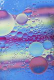 Oil drops in water macro with a colorful background royalty free stock photos