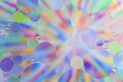 Oil drops in water macro with a colorful background royalty free stock images