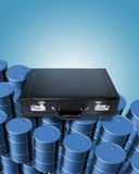 Oil drums and briefcase. New clean oil drums piled high with a business briefcase resting on them. Blue background Stock Photography