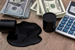 Oil drums on US dollars with calculator Royalty Free Stock Images