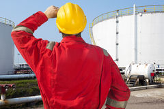 Oil Engineer. Looking at overdue maintenance and safety issues of storage tanks with crude oil supply Royalty Free Stock Image