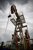 Oil exploration closeup low angle view. Oil rig pump dramaticly underexposed against contrast cloudy sky Royalty Free Stock Photography