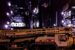 Oil factory building with air pollution and industrial car. The oil factory building with air pollution and industrial car at night Stock Photos