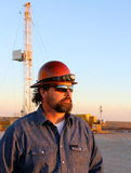 Oil field. Worker watching the sunset Royalty Free Stock Images