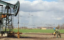Oil field. With pump jack and worker Stock Images