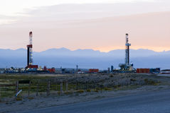Oil field. New oil and gas drilling activity in Wyoming, sunrise in the background Royalty Free Stock Photos