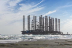Oil field at the Caspian Sea. Oil field derrick at the Caspian Sea with waves stock image