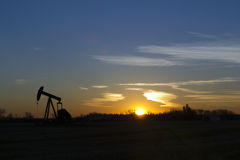 Oil Field at Dawn. Oil Equipment in a farm field during a sunrise Stock Photo