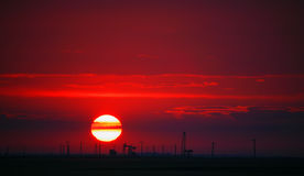 Oil field profiled on solar disc at sunset. Oil field profiled on solar disc and beautiful red sky at sunset Royalty Free Stock Photo