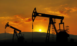 Oil field. And pump jack against sunset