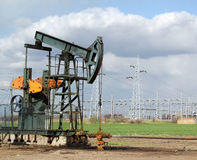 Oil field with pumpjack Stock Images