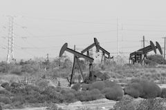 Oil Field. Oil pumps in a oil field with electrical towers in the background Royalty Free Stock Images