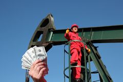 Oil Field Worker Salaries Concept. Hand holding US dollar bills in front of an oil worker at oil well pump jack Royalty Free Stock Image