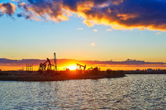 The oil fields and lake in the afterglow Royalty Free Stock Photos