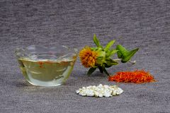 Oil, flower, inflorescences and seeds of wild saffron or gray burlap. Safflower. Rustic style. Copy space stock photo