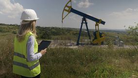 Oil forewoman engineer using a tablet pc to check maintenance schedule for oil pump unit -. Oil forewoman engineer using a tablet pc to check maintenance stock footage