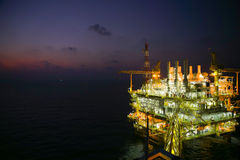 Oil and gas construction in night view. View from helicopter night flight. Oil and gas platform in offshore. Stock Photos