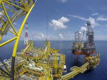 Oil and gas industry. Aerial view of oil and gas platform with jack-up rig in the middle of the sea with blue sky Stock Images