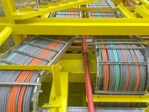 Oil and gas industry. High voltage electrical cables layout on cable tray and yellow steel structure at oil and gas platform royalty free stock image