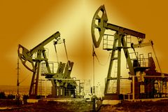 Oil and gas industry. Work of oil pump jack on a oil field. White clouds and blue sky. oil well pump.  Work of oil pump jack on a oil field stock photo