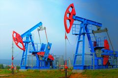 Oil and gas industry. Work of oil pump jack on a oil field. White clouds and blue sky. oil well pump.  Work of oil pump jack on a oil field royalty free stock image