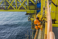 Oil and gas. Man working overboard. Abseiler climbing and hanging at the edge of oil and gas platform in the middle of sea royalty free stock photos