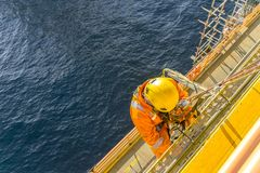 Oil and gas. Man working overboard. Abseiler complete with personal protective equipment PPE climbing the edge of oil and gas rig platform in the middle of sea royalty free stock photos