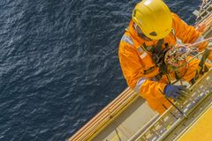 Oil and gas. Man working overboard. Abseiler complete with personal protective equipment PPE climbing and hanging at the edge of oil and gas rig platform in the royalty free stock photography